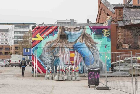 Colourful mural of super-nurse in mask