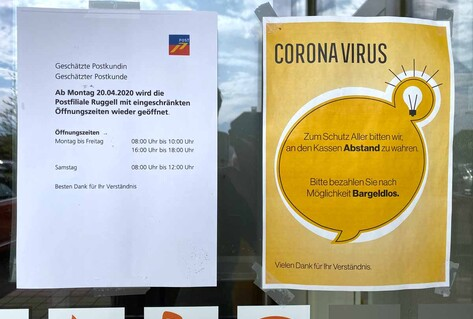 Two posters outside post office listing new measures