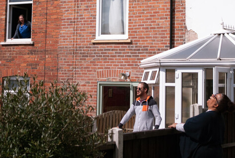 """PICTURING LOCKDOWN"", A GARDEN SCENE ON A SUNNY DAY WITH BLUE SKY, TWO PEOPLE LAUGING OVER GARDEN FENCES AS ANOTHER LOOKS DOWN FROM A FIRST FLOOR WINDOW ALSO LAUGHING."