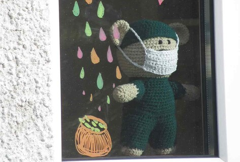 knitted leprechaun with mask in window