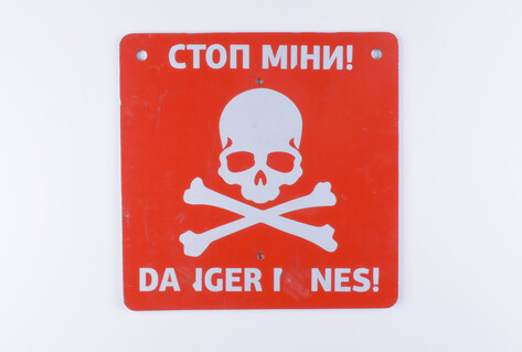 Warning sign about mines in a village