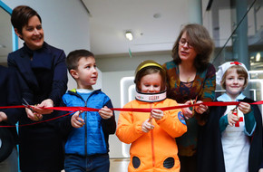 Young visitors cutting red ribbon