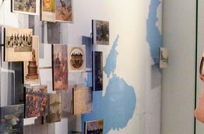 Visitor looking postcards museum display