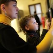 Jongen en moeder die museum bezoeken wat betreft interactief scherm