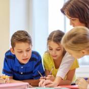 Kinderen die schoolwerk doen onder toezicht van een leraar