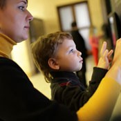 Boy and mother visiting museum touching interactive screen