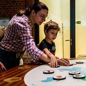 Момче и майка посещаващи музей докосват интерактивен екран