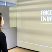 Woman in museum exhibition looking at Fake News display