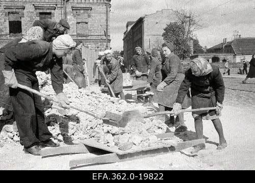 Black white photograph women clearing rubble