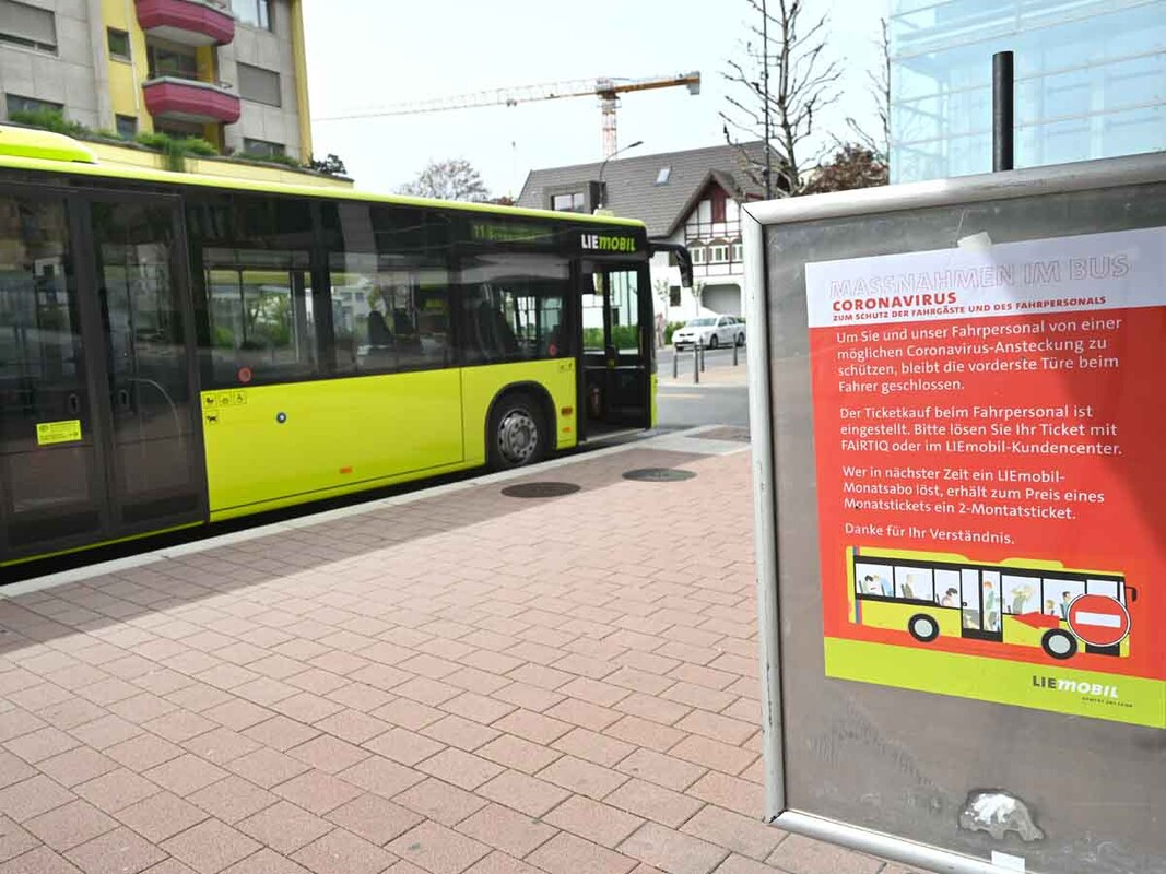 Yellow bus alongside poster with health measures