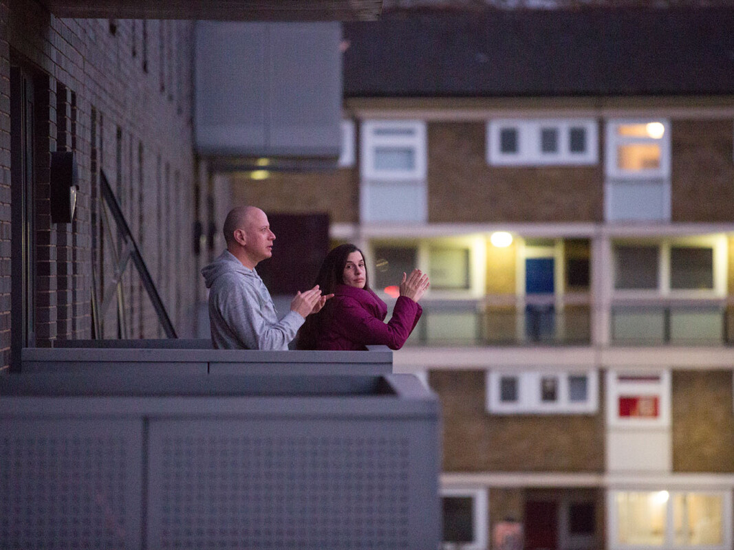 Man and woman outside flat clapping