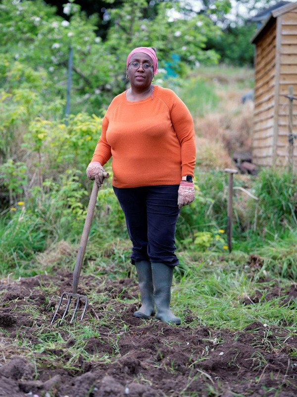 Woman standing in grass allotment with spade