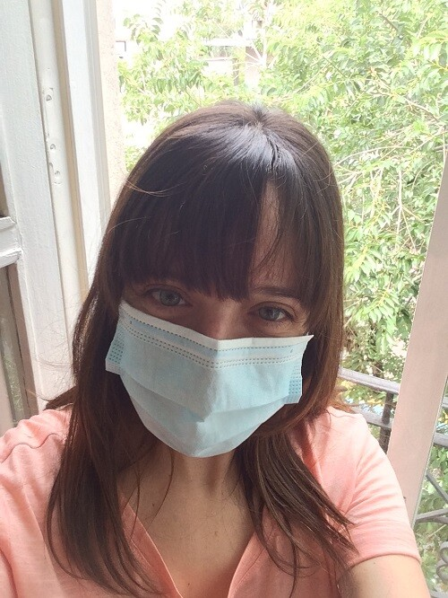 Young woman on balcony wearing mask